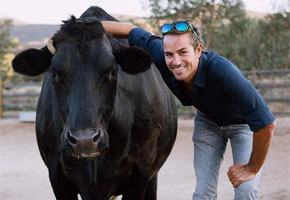 Bruno poses with a guest | Photo courtesy of Farm Sanctuary, Facebook